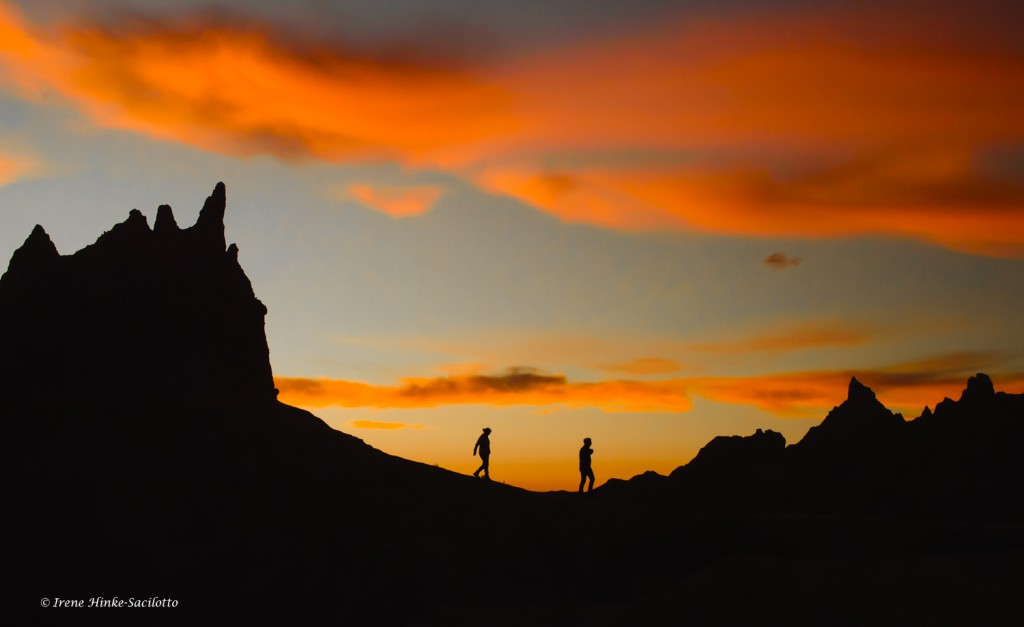 Hikers in the Badlands at sunset